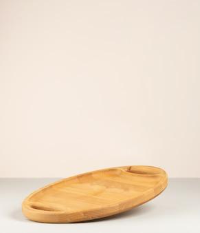 Pusta brązowa drewniana deska kuchenna na szarym tle papieru, naczynia