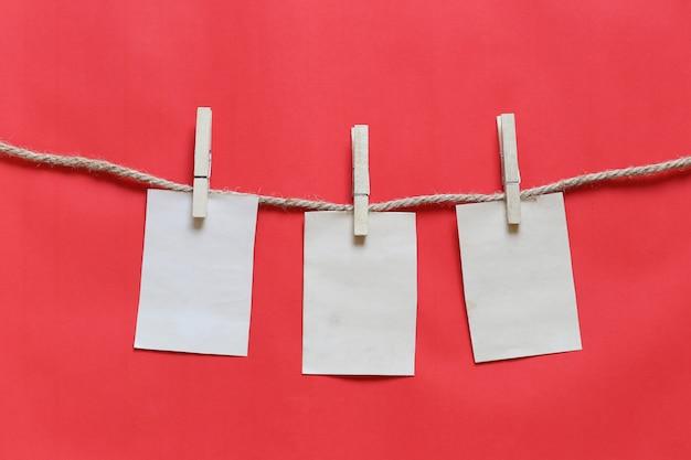 Pusta brązu notatka na clothesline i czerwonym tle.