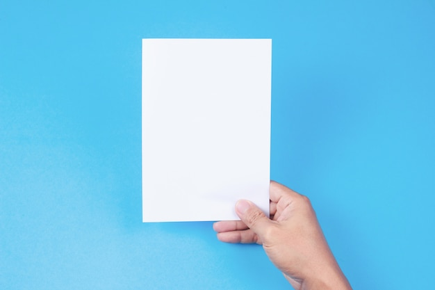 Pusta broszurka z pustym miejscem w ręce na błękitnym tle.