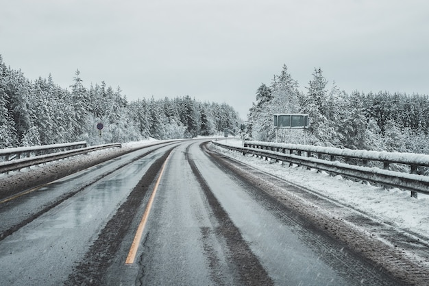 Pusta, brudna zimowa autostrada. zakręt na śliskiej drodze.