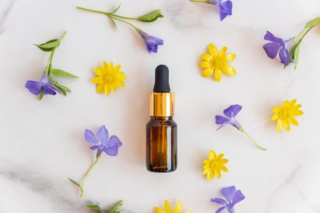 Pusta butelka olejku ze szkła bursztynowego z pipetą na marmurowej powierzchni ozdobiona kwitnącymi dzikimi kwiatami