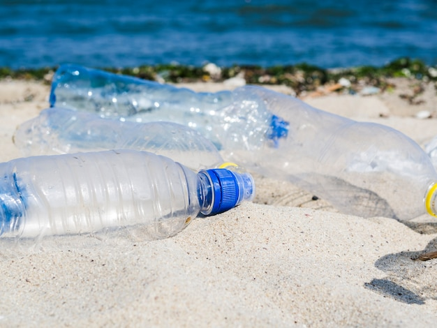 Pusta butelka ścieków na piasku na plaży