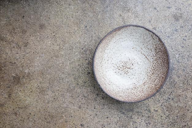 Pusta ceramiczna miska domowej roboty na szarym kamiennym tle, widok z góry