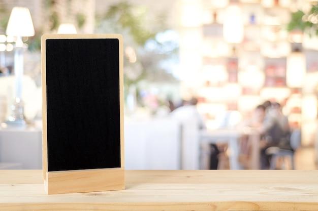 Pusta chalkboard pozycja na drewno stole nad plamy restauracją z bokeh tłem