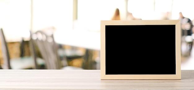 Pusta chalkboard pozycja na drewno stole nad plamy restauracją
