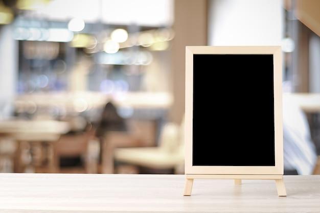 Pusta chalkboard pozycja na drewno stole z bokeh tłem