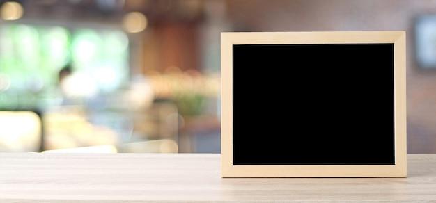 Pusta chalkboard pozycja na stole nad plama sklepem z bokeh tłem