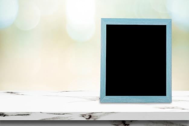 Pusta chalkboard pozycja na stole nad plamy kawiarnią z bokeh tłem