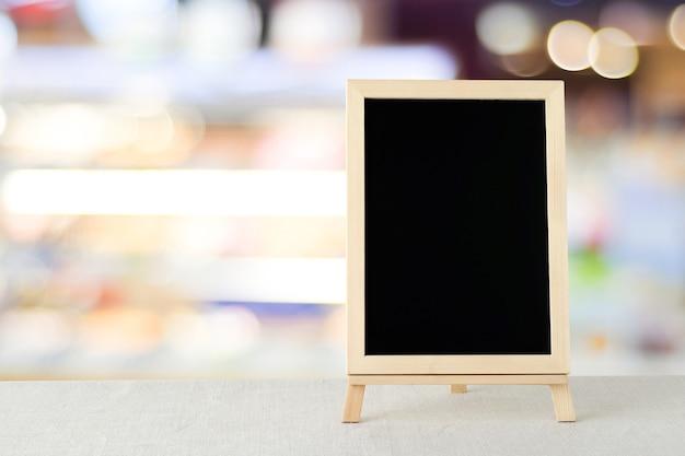 Pusta chalkboard pozycja na workowym tablecloth nad plama sklepem z bokeh tłem