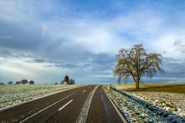 Pusta czarna asfaltowa droga między zielonymi polami
