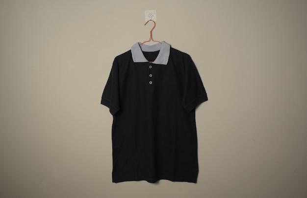 Pusta czarna koszulka dorywcza z szarym kołnierzem makieta na wieszaku w tle ściany widok z przodu