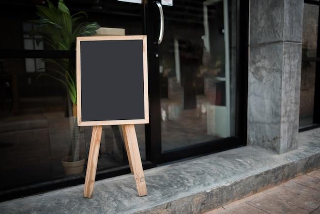 Pusta czarna kredowa deska przed kawiarnią