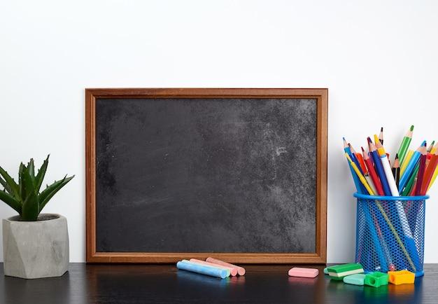 Pusta czarna tablica kredowa, kolorowe kredki w niebieskim metalowym stojaku na czarnym stole