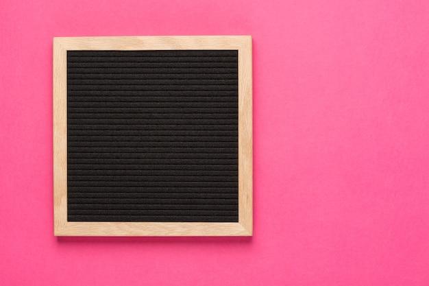 Pusta czarna tablica na różowym tle