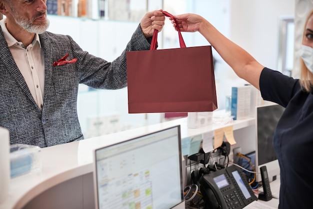 Pusta czerwona torba przekazywana od sprzedawcy do klienta