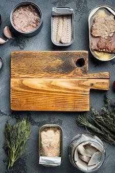 Pusta deska do krojenia w ramce z ryb w puszkach zestaw owoców morza, na szaro