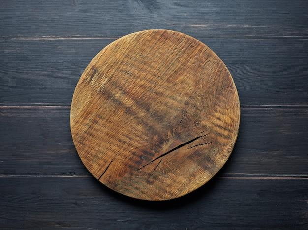 Pusta drewniana deska do krojenia na ciemnym stole w kuchni, widok z góry