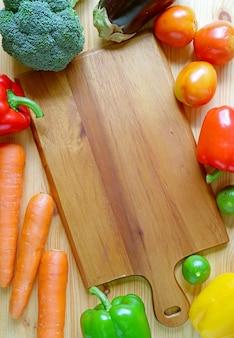 Pusta drewniana deska do krojenia otoczona kolorowymi świeżymi warzywami