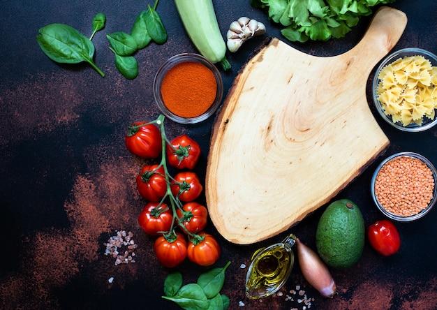 Pusta drewniana deska do krojenia otoczona różnymi surowymi warzywami, oliwą z oliwek, soczewicą, przyprawami, makaronem. wegańskie, wegetariańskie jedzenie, koncepcja zdrowego odżywiania. rustykalne tło, widok z góry, kopia przestrzeń