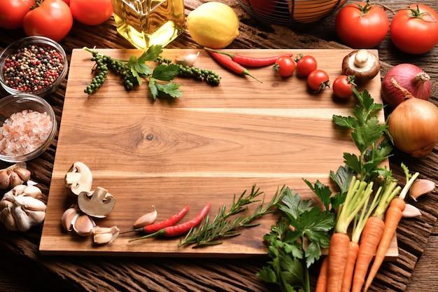 Pusta drewniana deska do krojenia z miejscem na kopię otoczona papryką, ziołami, pomidorami, grzybami i innymi pysznymi warzywami o smaku na stole