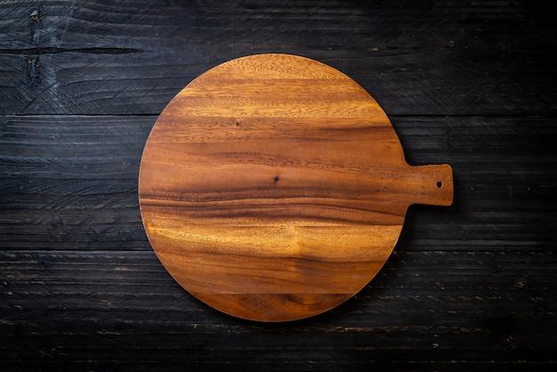Pusta drewniana deska do krojenia z ściereczką kuchenną