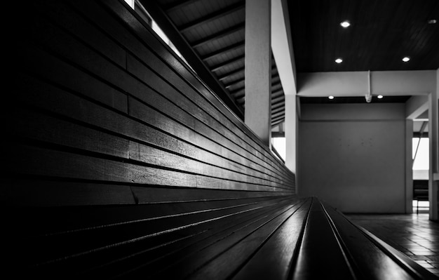 Pusta drewniana ławka w hotelu. widok perspektywiczny pustej drewnianej ławce na podłodze płytki. koncepcja oczekiwania lub przejścia na emeryturę. długie siedzisko do siedzenia i czekania. meble do nowoczesnego wystroju wnętrz. taras.