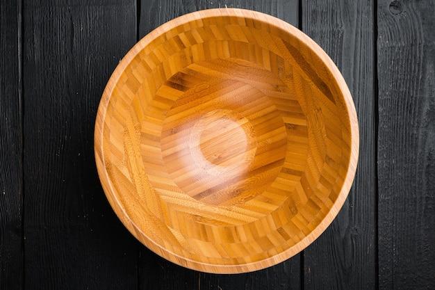 Pusta drewniana miska z kopią miejsca na tekst lub jedzenie, widok z góry płasko leżący, na tle czarnego drewnianego stołu