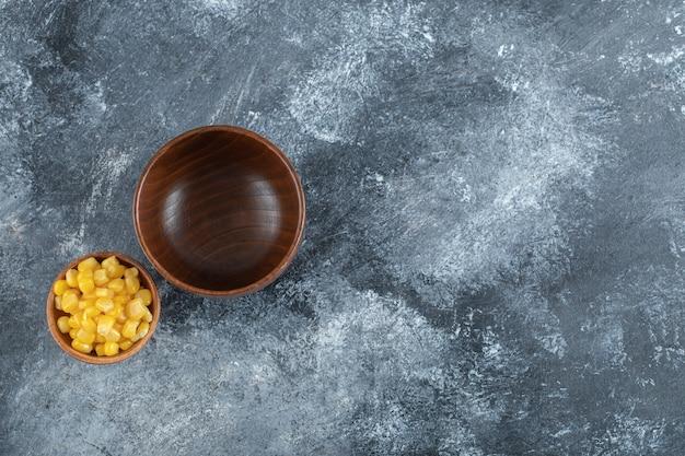 Pusta drewniana miska z małą miską ziaren popcornu.