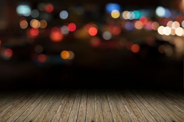 Pusta drewniana platforma stołowa i bokeh w nocy