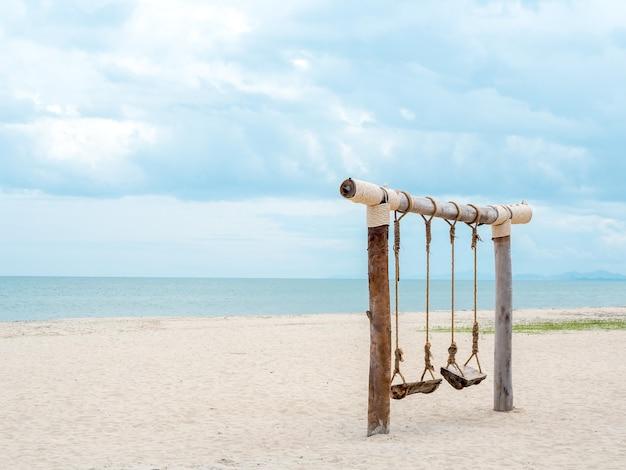 Pusta drewniana podwójna huśtawka na plaży na morzu, piasku, morzu i błękitnym niebie, minimalistyczny styl