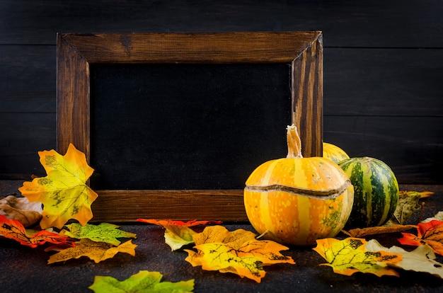 Pusta drewniana rama, dekoracyjne mini dynie z suszonych liści jesienią na ciemnym tle betonu, koncepcja jesień, miejsce, koncepcja jesień lub jesienne wakacje, święto dziękczynienia, miejsce.