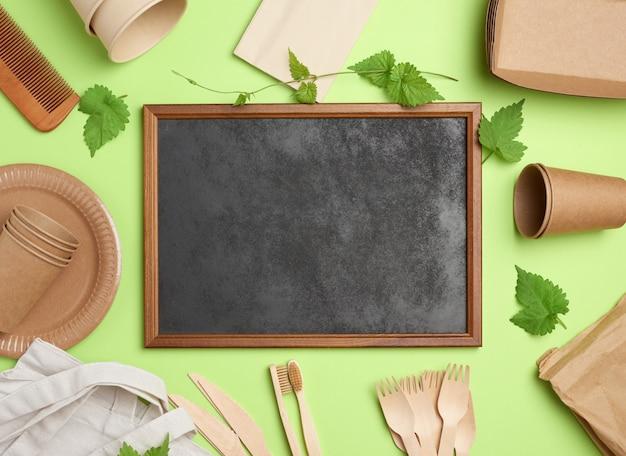 Pusta drewniana rama i jednorazowe papierowe talerze, kubki, drewniane widelce na zielonym tle