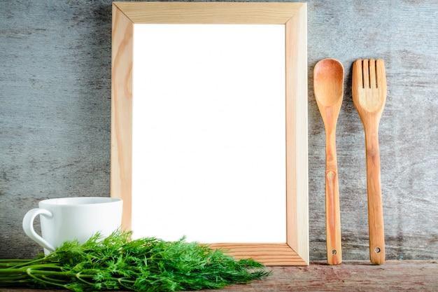 Pusta drewniana rama z odosobnionym białym tłem i kuchennymi naczyniami i zielonym koperem