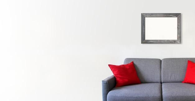 Pusta drewniana ramka na zdjęcia na białej ścianie nad sofą. minimalistyczne tło wnętrza. baner poziomy