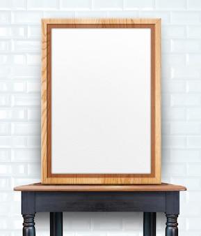 Pusta drewniana ramka na zdjęcia opierając się na białej błyszczącej płytki ścienne na vintage stół z drewna