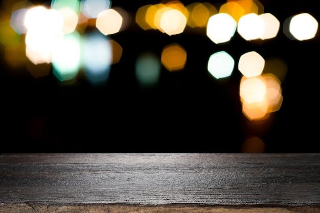 Pusta drewniana stołowa platforma i bokeh przy nocą