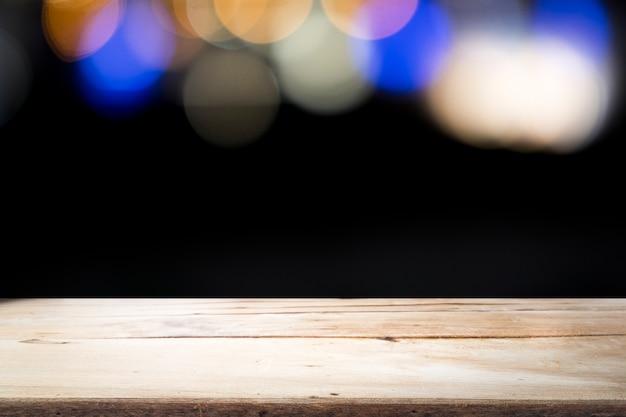 Pusta drewniana stołowa platforma na bokeh przy nocą.