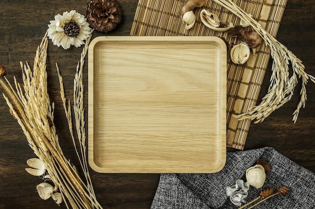 Pusta drewniana taca ozdobiona ryżem i płatkami zbożowymi na drewnianym stole
