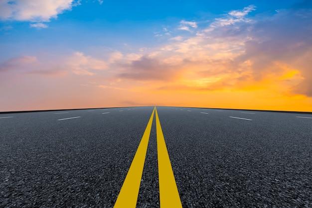 Pusta droga asfaltowa i naturalny krajobraz w zachodzącym słońcu