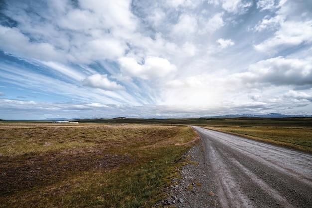 Pusta droga gruntowa przez wieś krajobrazu.