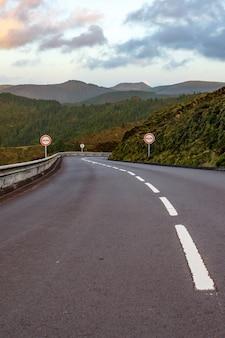 Pusta droga w górach. zachód słońca. żadnego znaku wyprzedzania