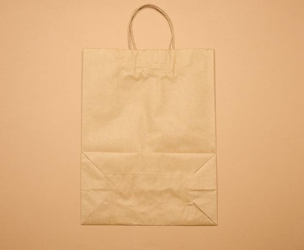 Pusta duża jednorazowa brązowa torba papierowa z uchwytami na brązowym tle, ekologiczne opakowanie, zero odpadów