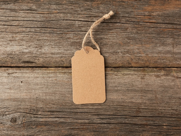 Pusta etykieta z brązowego papieru przewiązana białym sznurkiem. metka, metka na prezent