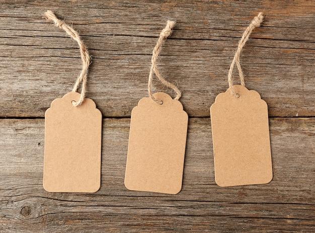 Pusta etykieta z brązowego papieru przewiązana białym sznurkiem. metka, prezent ta