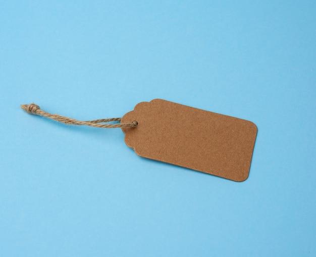 Pusta etykieta z brązowego papieru przewiązana białym sznurkiem. metka