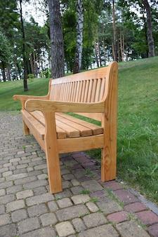 Pusta figurowa drewniana ławka w profilu stoi w letnim parku na kamiennej płycie chodnikowej
