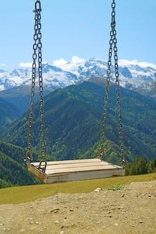 Pusta huśtawka przeciw rozmytej górze kaukazu, mestia, swanetia region gruzji