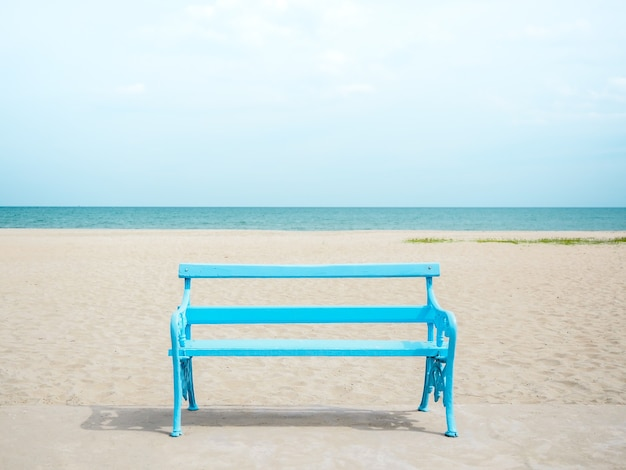 Pusta jasnoniebieska drewniana ławka na plaży, na morze, morze i błękitne niebo