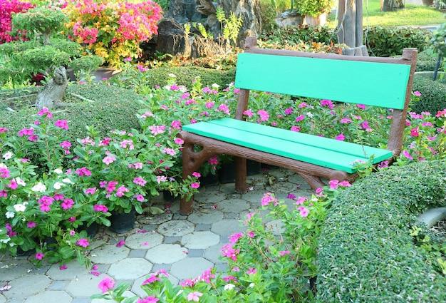 Pusta, jasnozielona drewniana ławka wśród żywych różowych krzewów kwitnących