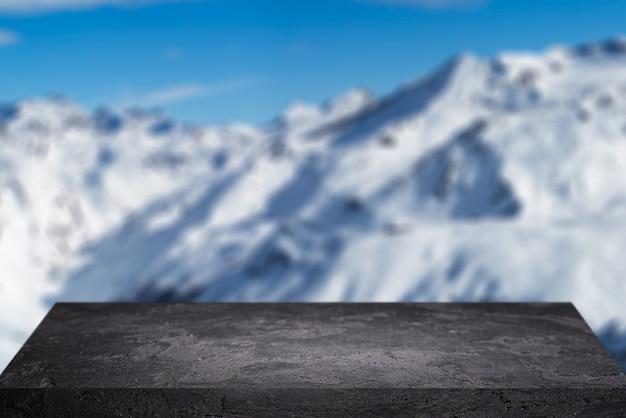 Pusta kamienna powierzchnia na rozmytym tle zaśnieżonego górzystego obszaru w zimowy dzień i błękitne niebo